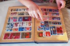 Ребенок смотрит альбом с печатями стоковые фотографии rf