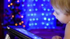 Ребенок смотрит к таблетке лежа на кровати На заднем плане, света и гирлянды ели рождества видеоматериал