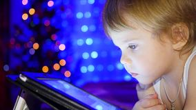 Ребенок смотрит к таблетке лежа на кровати На заднем плане, света и гирлянды ели рождества акции видеоматериалы