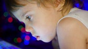Ребенок смотрит к таблетке лежа на кровати На заднем плане, света bokeh и гирлянды ели рождества видеоматериал