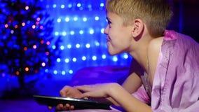Ребенок смотрит к ТВ лежа на кровати На заднем плане, света и гирлянды ели рождества сток-видео