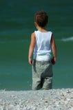 ребенок смотря прибой стоковое фото rf