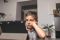 Ребенок смотря таблетку с выражением на серьезной стороне стоковая фотография rf