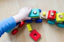 Ребенок собирает поезд игрушки деревянный Стоковое фото RF