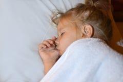 Ребенок сосет палец в кровати перед временем ложиться спать и во время сна стоковые фотографии rf