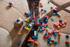 Ребенок стоит в середине комнаты и много разбросанные игрушки вокруг стоковое фото rf