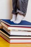 Ребенок стоя на стоге книг Стоковые Фото