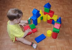 Ребенок строит замок из пластичного дизайнера Игра с дизайнером Стоковое фото RF