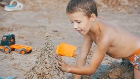 Ребенок строит замок песка на пляже в замедленном движении сток-видео
