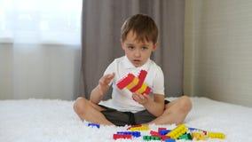 Ребенок строит от покрашенных блоков сидя на кровати в комнате Младенец и игрушки сток-видео