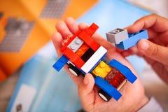 Ребенок строя автомобиль Lego Некоторые инструкции Lego на ба Стоковая Фотография