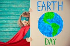Ребенок супергероя коричневейте покрытую землю дня относящое к окружающей среде листво идет идя зеленый вал текста лозунгов выска Стоковое фото RF