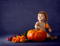 Ребенок с большой тыквой над пурпуровой предпосылкой. стоковые фото