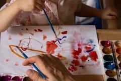 Ребенок с взрослым приниматься краски чертежа Стоковое фото RF