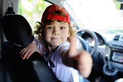 Ребенок с вьющиеся волосы и красной крышкой сидит за колесом автомобиля Стоковые Изображения
