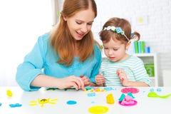 Ребенок с его матерью ваяет от глины Стоковое Изображение