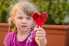 Ребенок с леденцом на палочке сердца Стоковые Фотографии RF