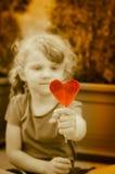 Ребенок с леденцом на палочке сердца Стоковые Изображения