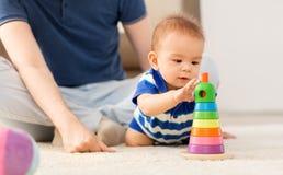 Ребенок с игрушкой отца и пирамиды дома стоковое изображение rf