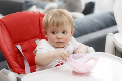 Ребенок с кашой сидеть и еды голубых глазов белокурой стоковые фотографии rf