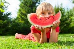 Ребенок с куском дыни внешним стоковые фотографии rf