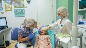 Ребенок с матерью на приеме ` s дантиста Девушка лежит в стуле, за ее матерью Доктор работает с Стоковые Фото