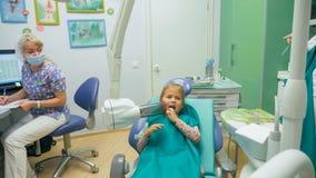 Ребенок с матерью на приеме ` s дантиста Девушка лежит в стуле, за ее матерью Доктор работает с Стоковая Фотография RF