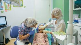Ребенок с матерью на приеме ` s дантиста Девушка лежит в стуле, за ее матерью Доктор работает с Стоковое Изображение RF
