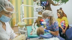 Ребенок с матерью на приеме ` s дантиста Девушка лежит в стуле, за ее матерью Доктор работает с Стоковые Фотографии RF