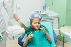 Ребенок с матерью на приеме ` s дантиста Девушка лежит в стуле, за ее матерью Доктор работает с Стоковое Фото