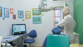 Ребенок с матерью на приеме ` s дантиста Девушка лежит в стуле, за ее матерью Доктор работает с Стоковые Изображения