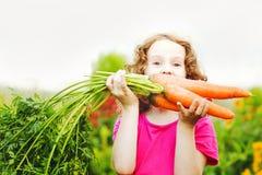 Ребенок с морковью в саде Стоковые Фотографии RF