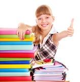 Ребенок с стогом книг и показывать большого пальца руки вверх. Стоковая Фотография RF