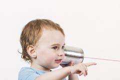 Ребенок с телефоном жестяной коробки Стоковое фото RF