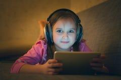 Ребенок слушает к музыке на наушниках Стоковое Фото
