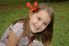 Ребенок с цветком в волосах   Стоковое Изображение