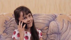 Ребенок с чернью Маленькая девочка в красивом платье с мобильным телефоном Девушка в платье с сердцами сток-видео