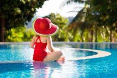 Ребенок с шляпой в бассейне тропическая каникула стоковые фотографии rf