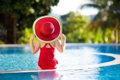 Ребенок с шляпой в бассейне тропическая каникула стоковые изображения