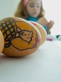 ребенок украшая пасхальные яйца Стоковые Изображения