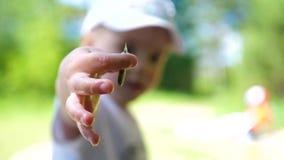 Ребенок уловил малую рыбу, держа рыб в его руках конец вверх Красивейший ландшафт лета воссоздание обеда напольное видеоматериал