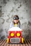 Ребенок управляя в автомобиле сделанном из картонной коробки Стоковое фото RF