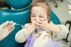 Ребенок устрашенный аппаратурами дантистов закрывает глаза и рот Стоковое Изображение RF