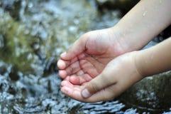 Ребенок черпает вверх чистую воду с его руками в реке Стоковое фото RF
