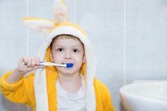 Ребенок чистя его зубы щеткой в ванной комнате стоковое фото
