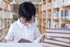 Ребенок читает книги на столе в библиотеке Стоковое Изображение