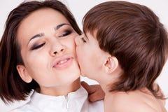 Ребенок bitting его щека мати Стоковые Изображения