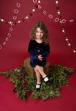 Ребенок Chirstmas на пне дерева и ветвях сосны, красном празднике Стоковая Фотография