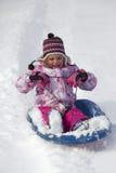 Ребенок sledding вниз с холма снега Стоковая Фотография