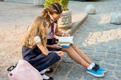 Ребеята школьного возраста, девушки максимума и начальная школа совместно прочитали учебник Время после школы на тротуаре улицы Стоковое Изображение RF